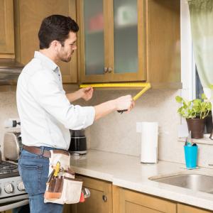 A man measuring a kitchen cabinet