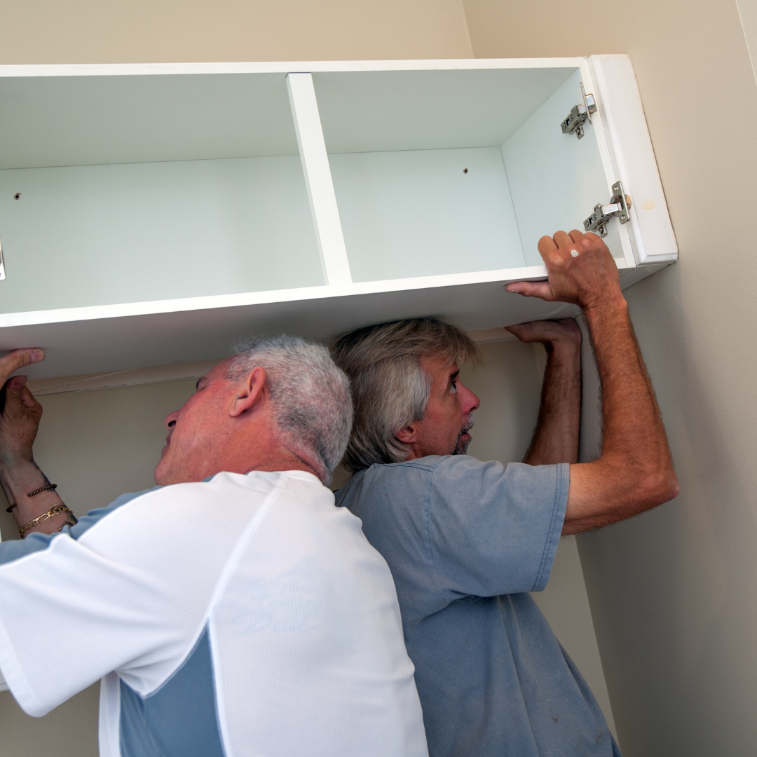 Two men refacing kitchen cabinets